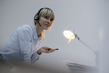Businesswoman having a conference call with headset - JOSF03256
