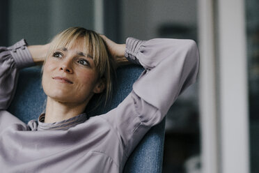 Blond woman relaxing in armchair, with hands behind head - JOSF03265