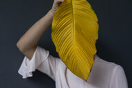 Woman covering face with a yellow banana leaf - JOSF03274