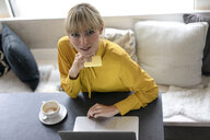 Blond woman doing online payment with her credit card - JOSF03277