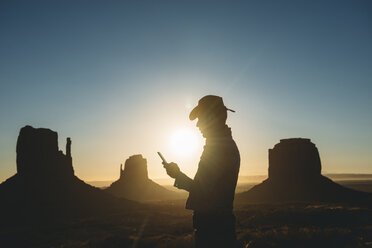 USA, Utah, Monument Valley, silhouette of man with cowboy hat looking at mobile phone at sunrise - GEMF02898
