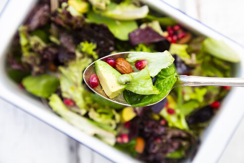 Detox salad bowl with avocado, pomegranate seeds, roasted soybeans, sunflower seeds and nuts, on spoon - LVF07870
