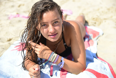 Portrait of teenage girl with wet hair lying on towel on the beach - MIZF00799
