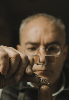 Artisan looking at ring with gemstone, portrait - AHSF00007