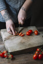 Young woman cutting tomatoes on chopping board - ALBF00802