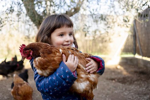 Portrait of smiling toddler girl holding chicken - GEMF02905