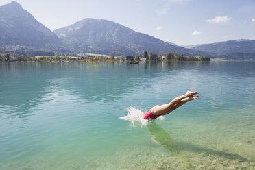 Austria, Alps, Salzburg, Salzkammergut, Salzburger Land, Wolfgangsee, woman jumping into lake - GWF06015