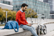 Casual businessman sitting on a bench in the city, using his smartohone and earphones - JRFF02825