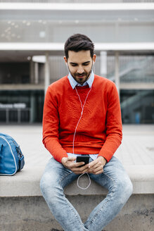 Casual businessman sitting on a bench in the city, using his smartohone and earphones - JRFF02828