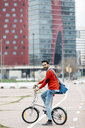 Casual businessman commuting in the city, using his folding bike - JRFF02846