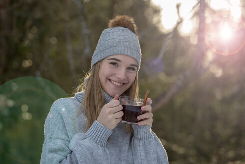 Portrait of smiling young woman with cup of tea in the woods - LBF02437