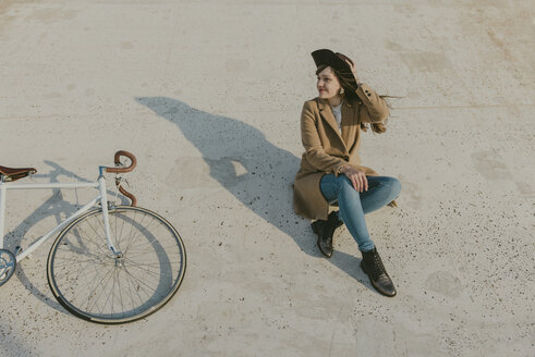 Young hipster woman sitting near to a bicycle - AHSF00045