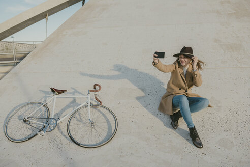 Young hipster woman near to a bicycle making a selfie - AHSF00051