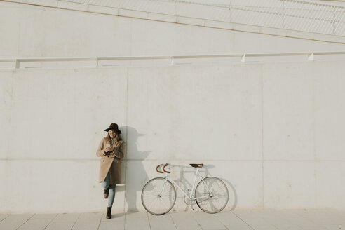 Young hipster woman leaning next to a bicycle, holding a phone - AHSF00060