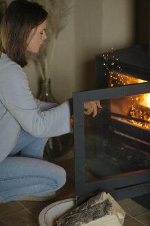 Woman using fire hook for poking open fire - ALBF00819