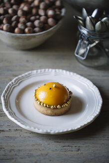 Decorated tarlet with peach half on plate - ALBF00837