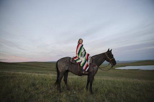 Portrait female rancher on horseback wrapped in blanket - HEROF28725