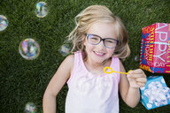 Overhead view portrait smiling girl blowing bubbles - HEROF28728