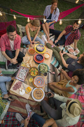 Overhead view friends enjoying backyard dinner party - HEROF28734