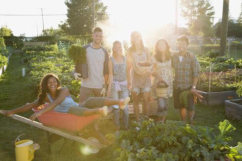 Portrait smiling friends harvesting vegetables in community garden - HEROF28749