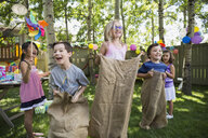 Kids enjoying sack race at backyard birthday party - HEROF28836