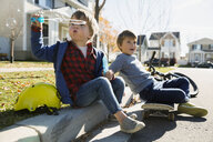 Brothers blowing bubbles on neighborhood curb - HEROF28908