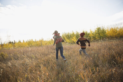 Brother and sister running in autumn field - HEROF28947