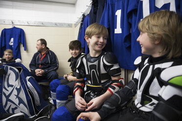 Smiling boy ice hockey players putting on protective sportswear in locker room - HEROF28962