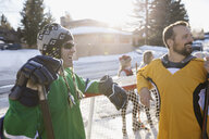 Smiling men playing ice hockey in sunny, snowy driveway - HEROF28965