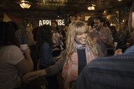Smiling woman dancing at music concert party - HEROF28983