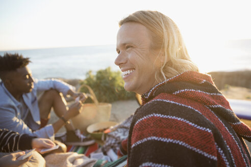 Smiling man hanging out with friends on sunset beach - HEROF29103