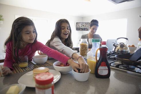 Smiling sisters eating breakfast in kitchen - HEROF29115