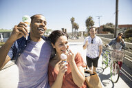 Smiling couples eating ice cream cones and walking on sunny California sidewalk - HEROF29139