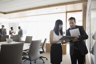 Businessman and businesswoman with digital tablet talking in conference room - HEROF29247