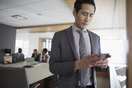 Businessman texting with cell phone in conference room - HEROF29250