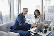 Businessman and businesswoman working, meeting at laptop in urban, highrise office - HEROF29301