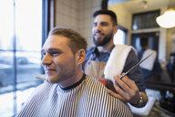 Barber with scissors behind male client in barbershop - HEROF29304