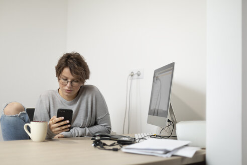 Young woman using smartphone at home, working space - VGF00228