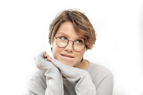 Portrait of thinking young woman with glasses and wireless earphones - VGF00231