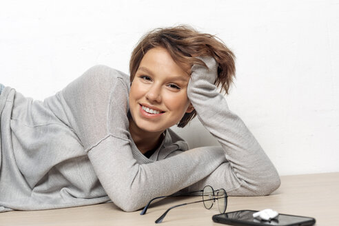Portrait of smiling young woman lying on the floor - VGF00237