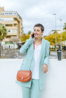 Woman dressed in jacket suit using smartphone, with thermo mug - KIJF02421