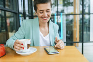 Woman in bar with mobile phone and coffee cup - KIJF02442