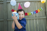 Enthusiastic boy wearing birthday party hat holding gift - HEROF29350
