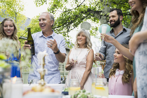 Family drinking celebrating with champagne at garden party - HEROF29353