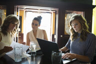 Businesswomen working with laptop in pub - HEROF29374
