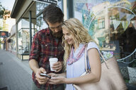 Couple texting with cell phone outside storefront - HEROF29425