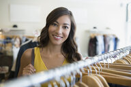 Portrait smiling woman in clothing shop - HEROF29437