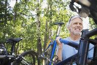 Senior man lifting mountain bike from rack - HEROF29449