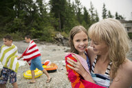 Portrait smiling mother holding daughter wrapped towel beach - HEROF29518
