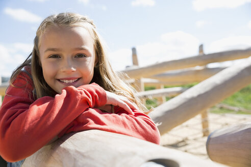 Portrait smiling girl leaning on log sunny playground - HEROF29521